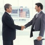 two members of an IT management firm shake hands at a business meeting